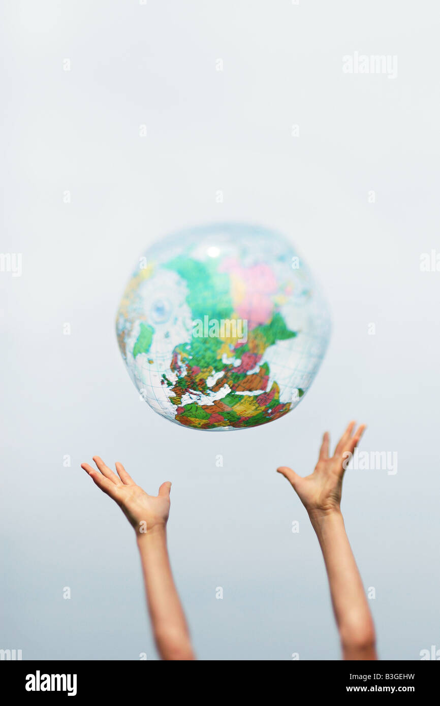 hands catching an inflatable globe - Stock Image