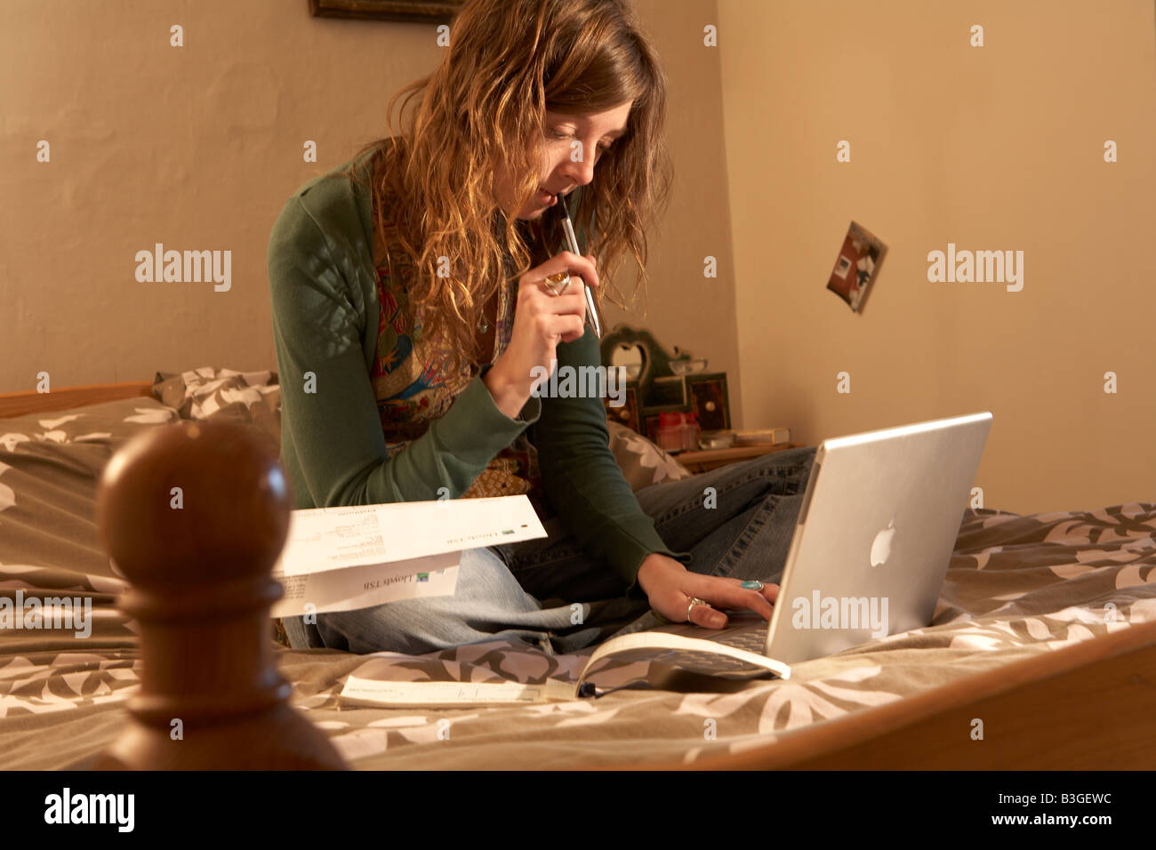 STUDENT SITTING ON A BED WITH COMPUTER TRYING TO BALANCE HER FINANCES - Stock Image