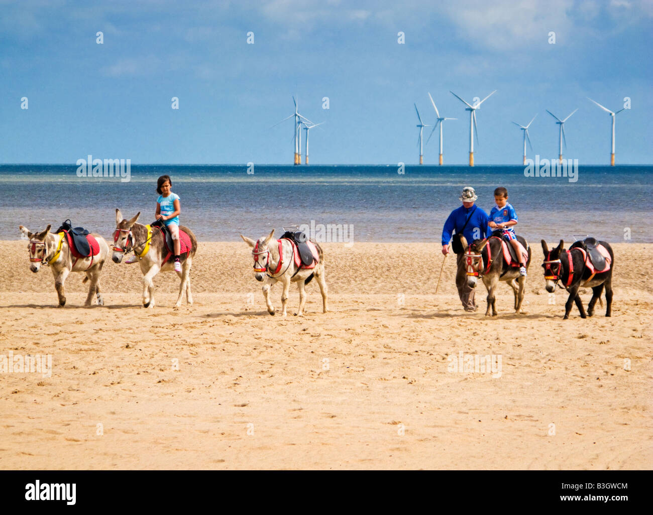 Children riding donkeys on the sands at Skegness beach, Lincolnshire, England, UK - with offshore windfarm Stock Photo