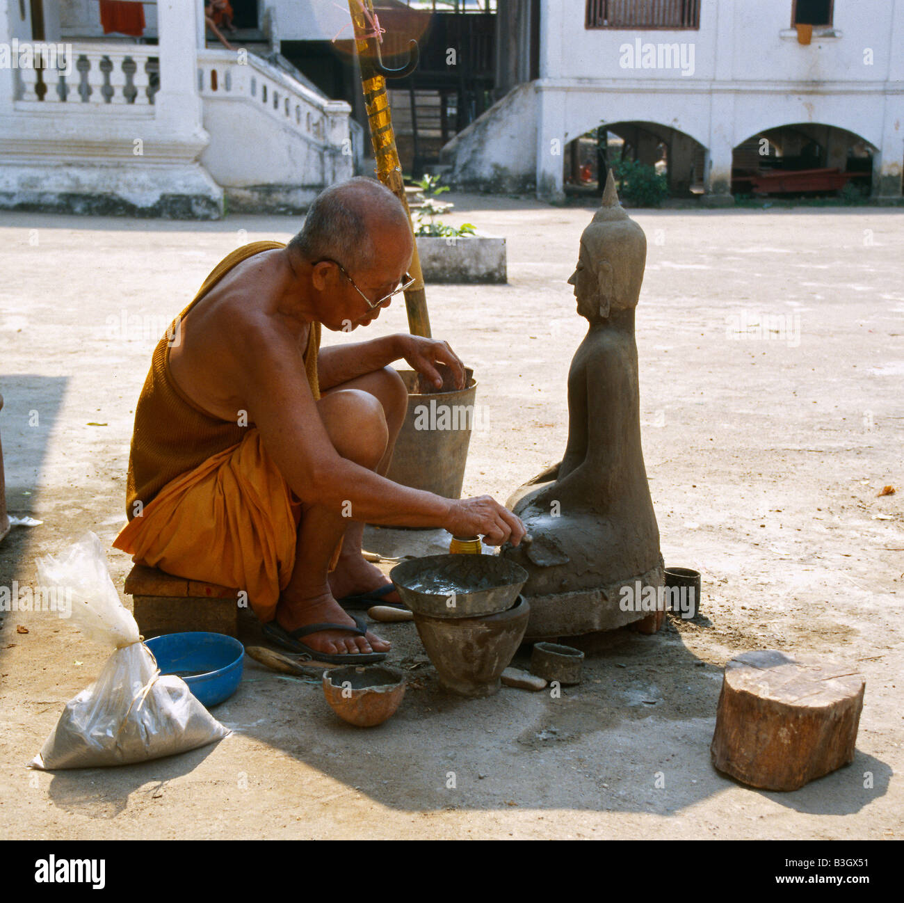 A monk is modelizing a Buddha statue out of plaster Luang Prabang Laos Stock Photo