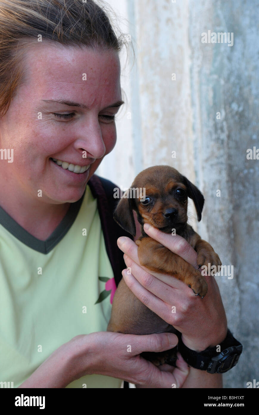 Younger smiling woman holding a puppy Villa Clara Province Cuba April 2007 Stock Photo