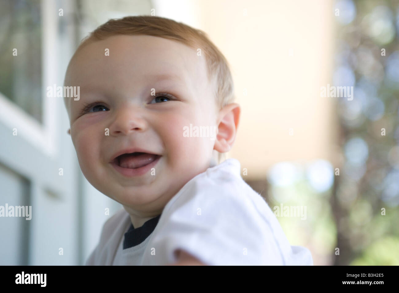 close up of eight month old baby smiling outdoors, confidence, joy, laughter Stock Photo