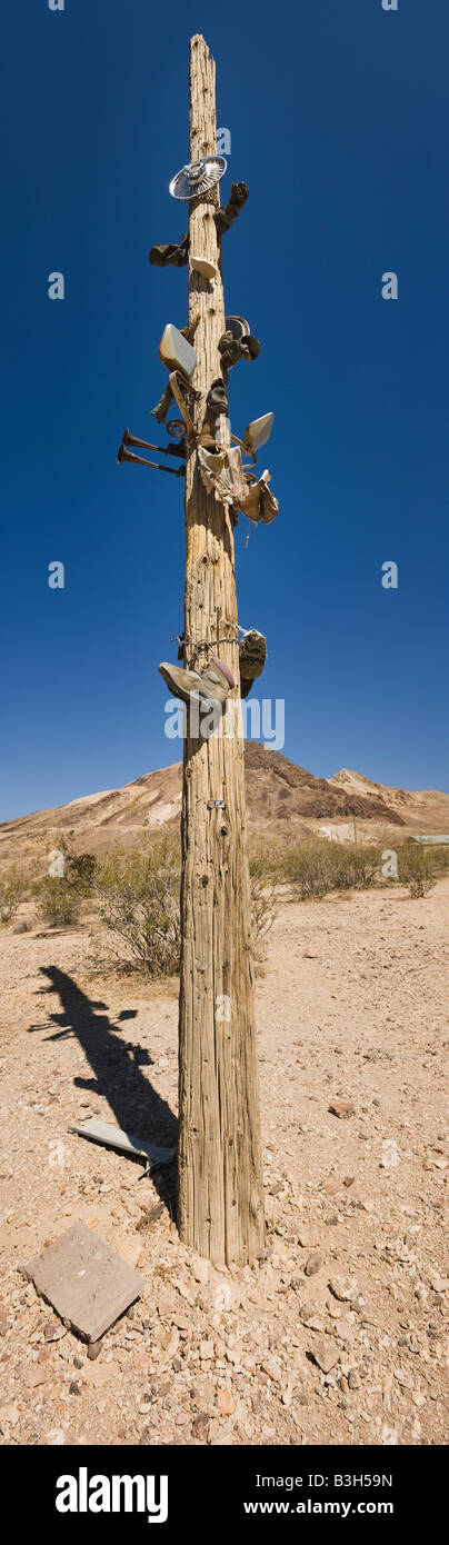 Telegraph pole with car parts and shoes. Rhyolite, Nevada, USA. Stock Photo