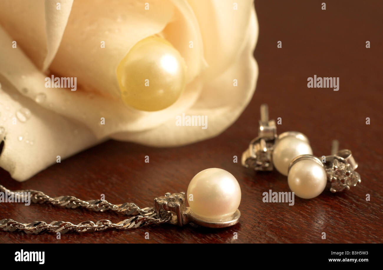 Wedding Jewelry on a dark wooden table with white rose in the background Stock Photo