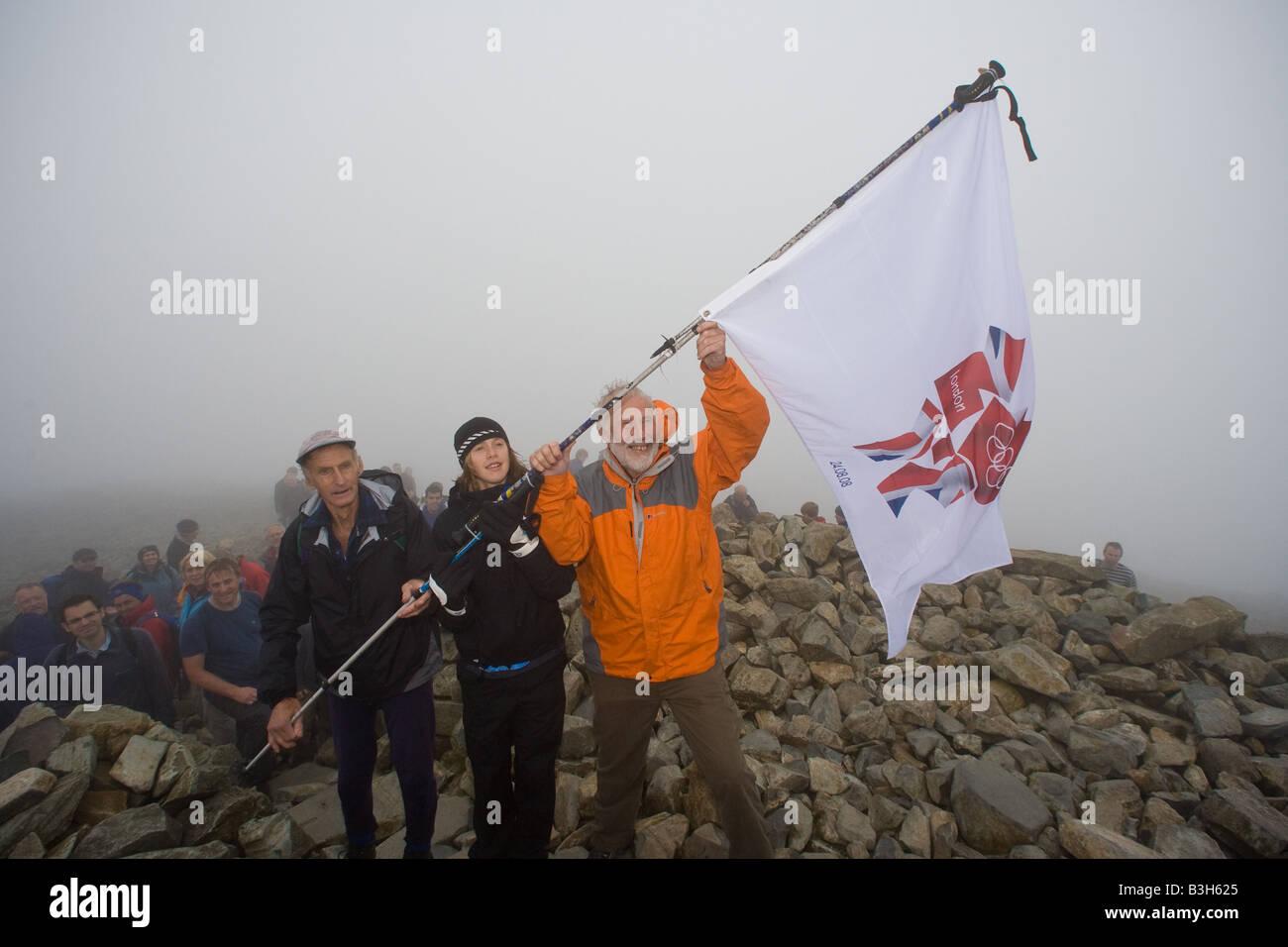 Sir Chris Bonington raises the London 2012 flag with fellrunner Jos Naylor and long distance runner Laura Park on - Stock Image