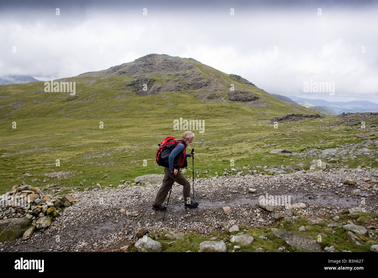 Sir Chris Bonington walks towards the summit of Scafell Pike, England's highest mountain. In the background - Stock Image