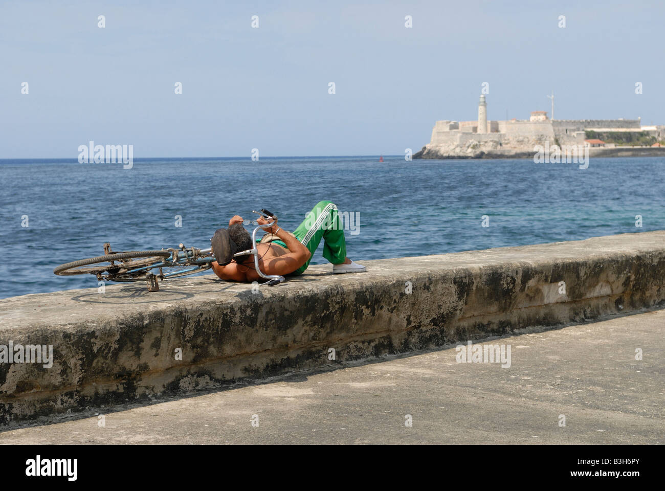 Cuban man with bicycle lying on a wall at the Malecon Boulevard in Havana Cuba April 2007 Stock Photo
