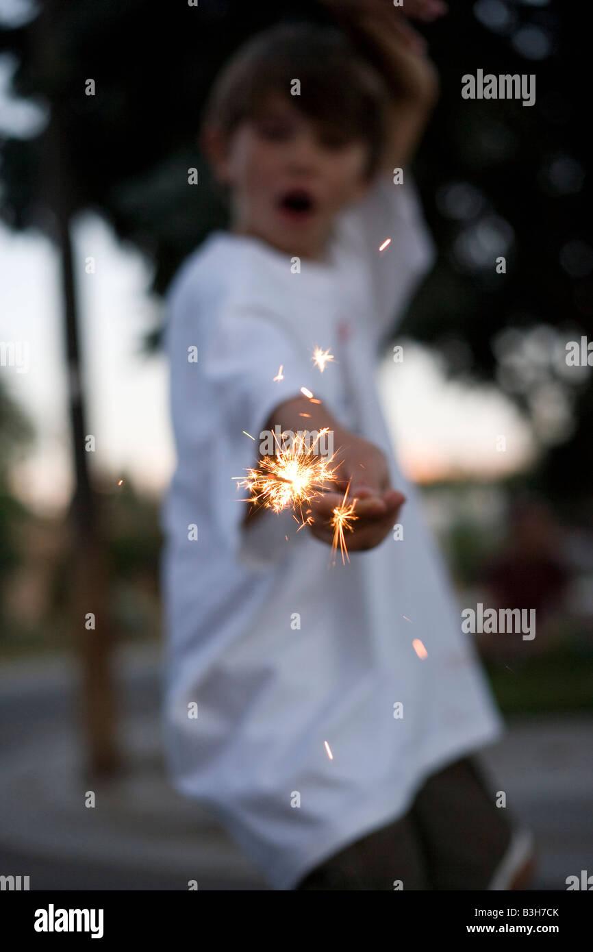 close up of child holding a sparkler burning, july fourth, celebration, eight year old boy - Stock Image