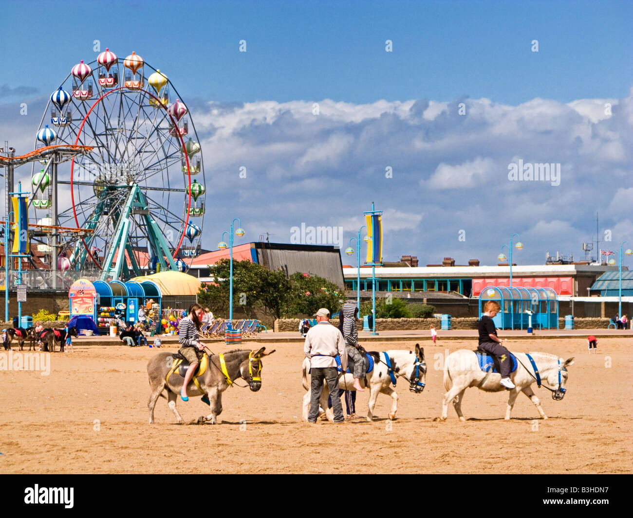 Children riding donkeys on Skegness beach, Lincolnshire, England, UK - Stock Image