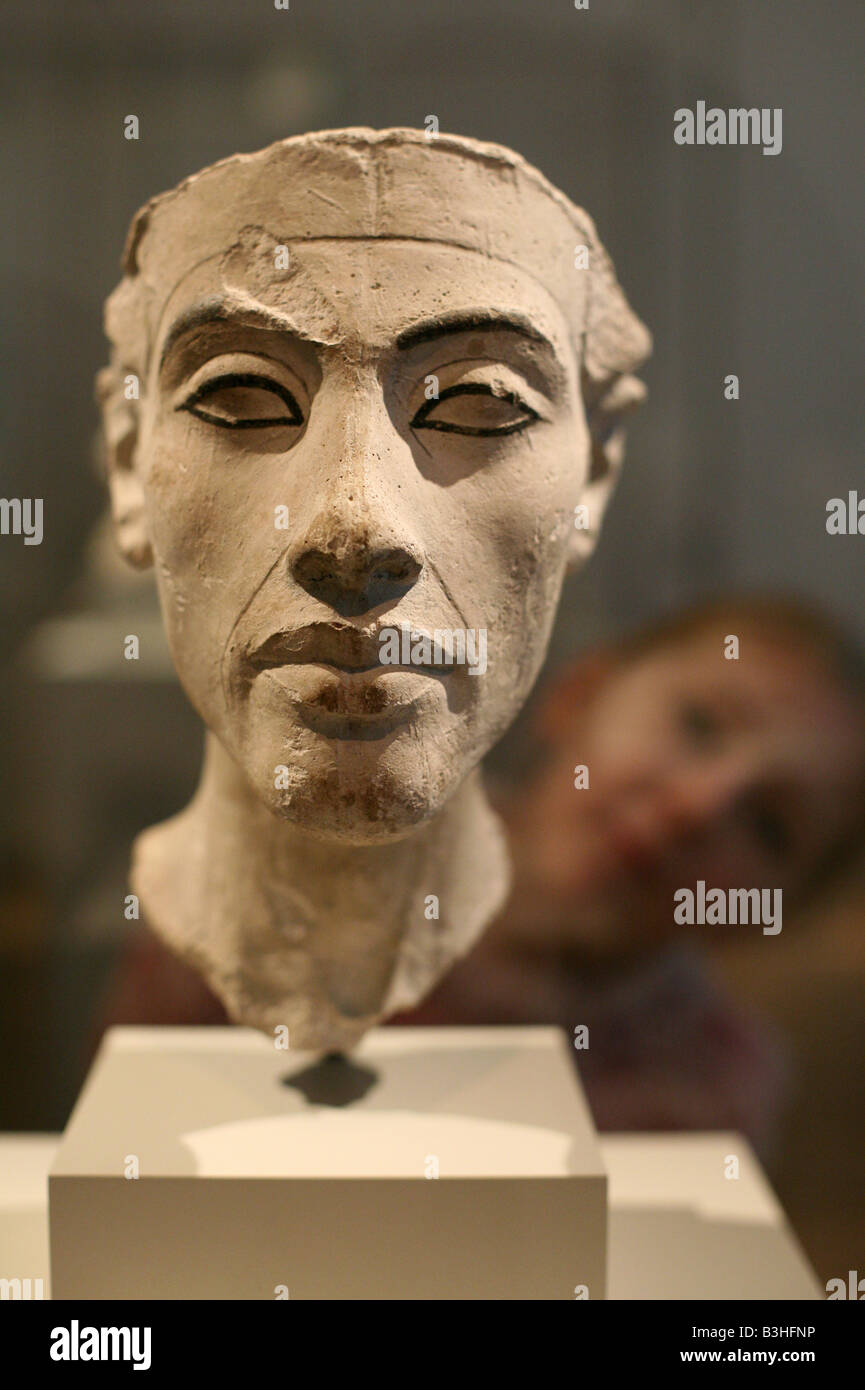 Young visitor looking at the bust of Pharaoh Akhenaten in the Egyptian Museum in Berlin Germany - Stock Image