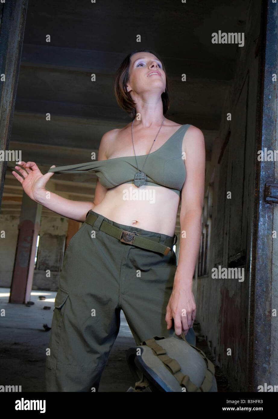 young woman posing in army uniform - Stock Image