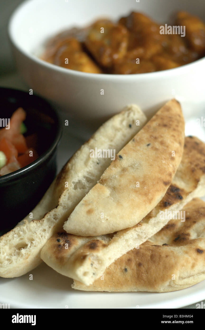A big bowl of Rogan Josh curry with a small salad and a naan bread - Stock Image