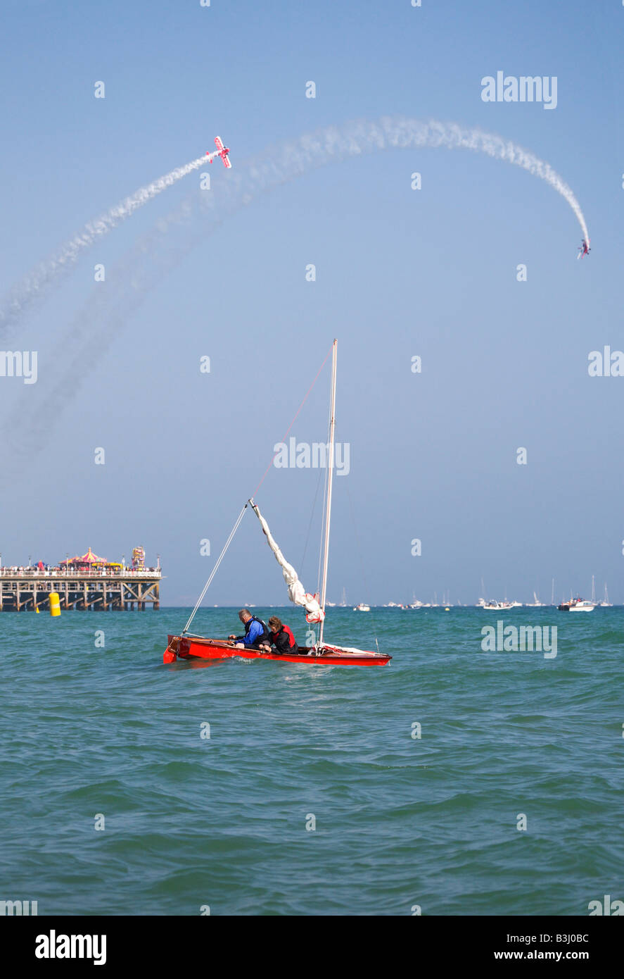 A couple in a sailing boat off Bournemouth beach, during the Bournemouth Air Festival. Bi-plane display over the Stock Photo