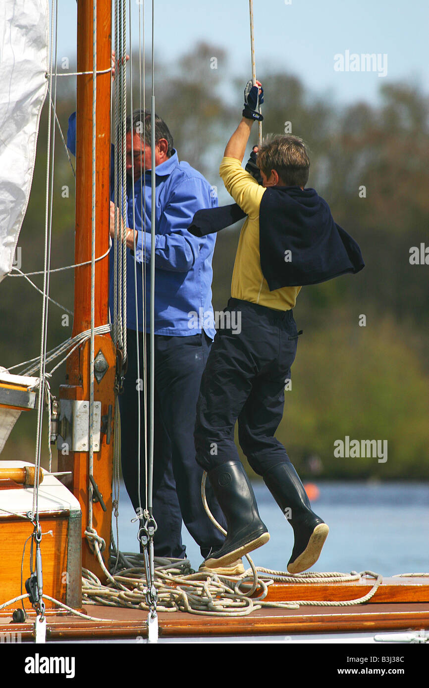 Hoisting the mainsail on a Broads cruiser. - Stock Image