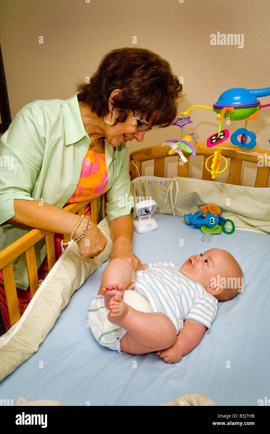 Babysitting her 6 month old grandson a grandmother in Laguna Niguel California interacts with the child  Note nannycam - Stock Image