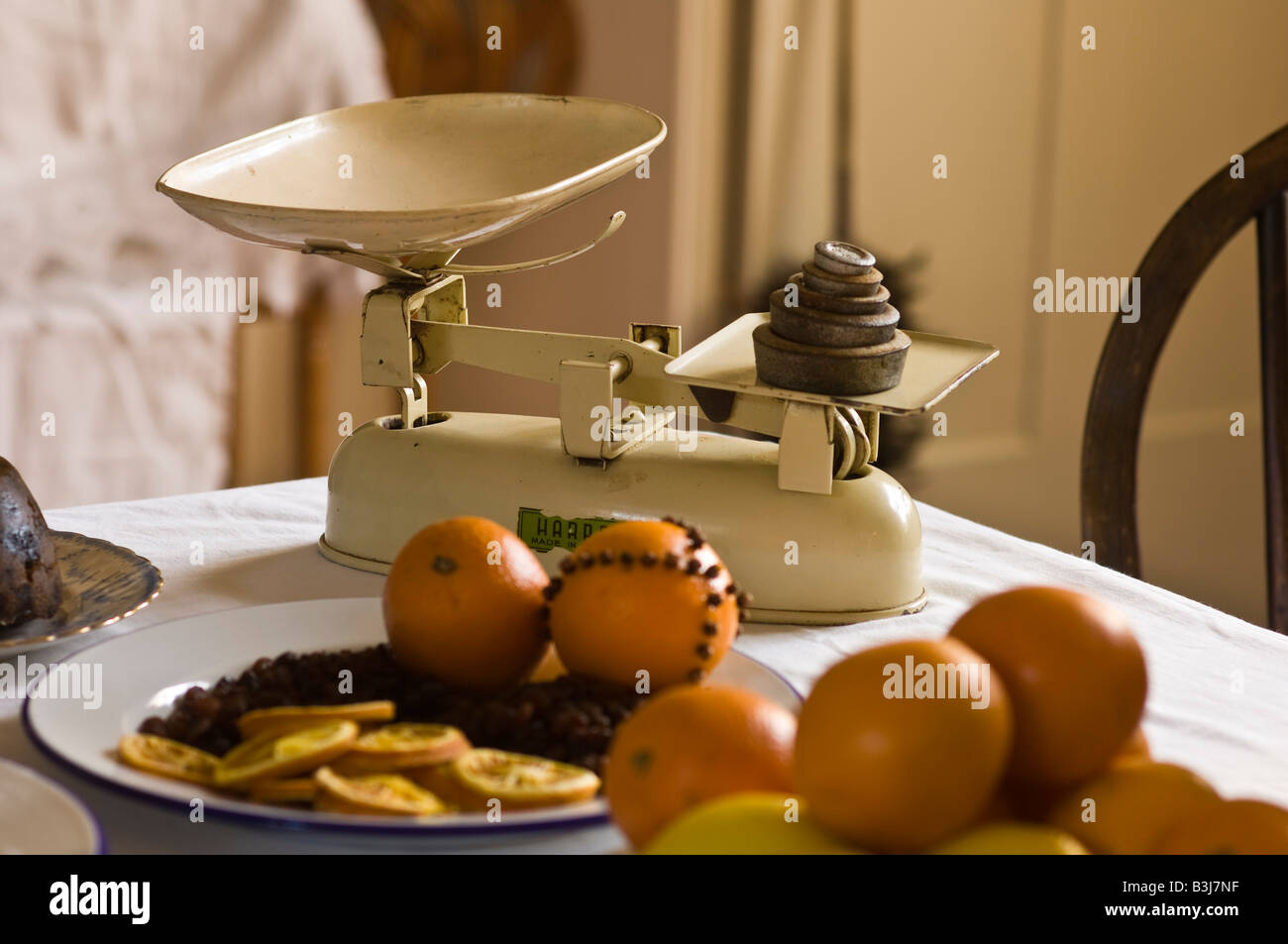 Old-fashioned weighing scales with oranges in a Victorian kitchen Stock Photo