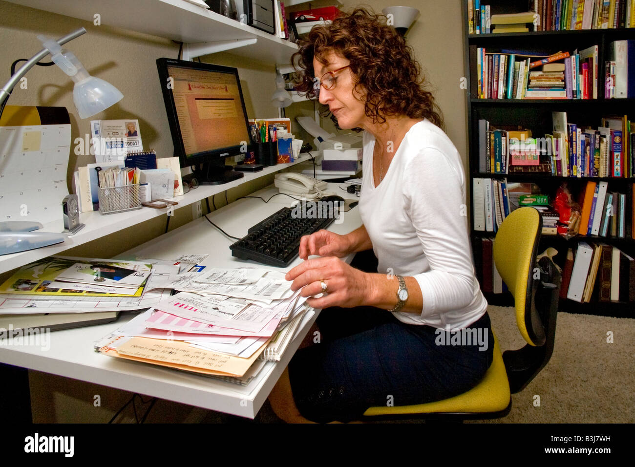 A 50 year old self employed woman works in her home office in Mission Viejo California Stock Photo