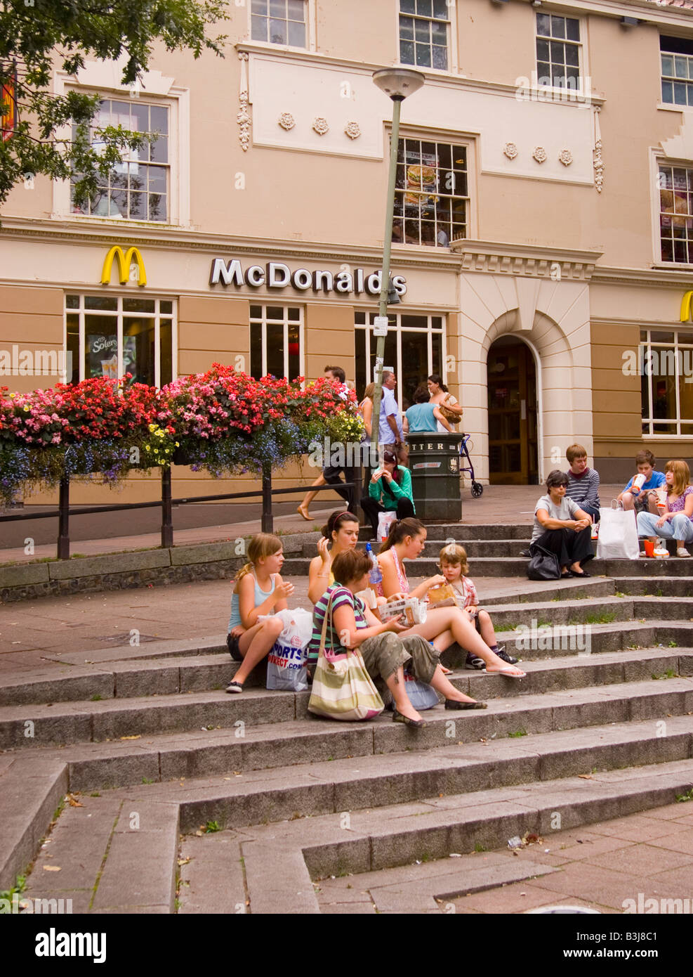 People eating their lunch on the steps outside Mcdonald's ...