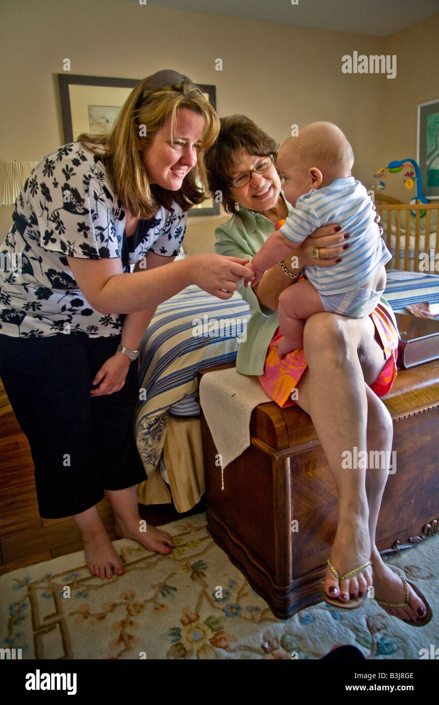 Babysitting her 6 month old grandson a grandmother and a relative in Laguna Niguel California interact with the - Stock Image