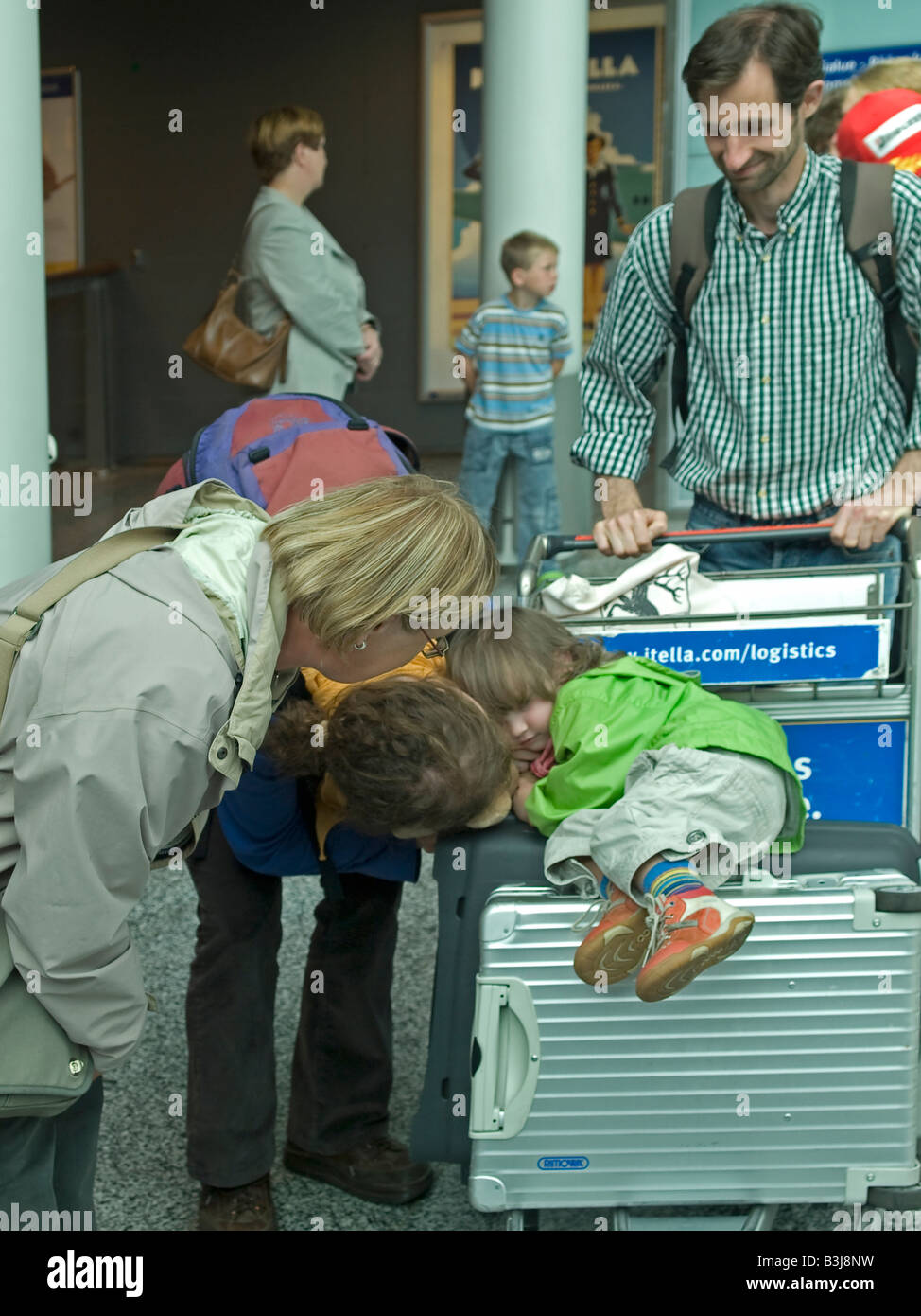 young family with a shy child on luggage passangers in arrival area of the international terminal of the Helsinki - Stock Image