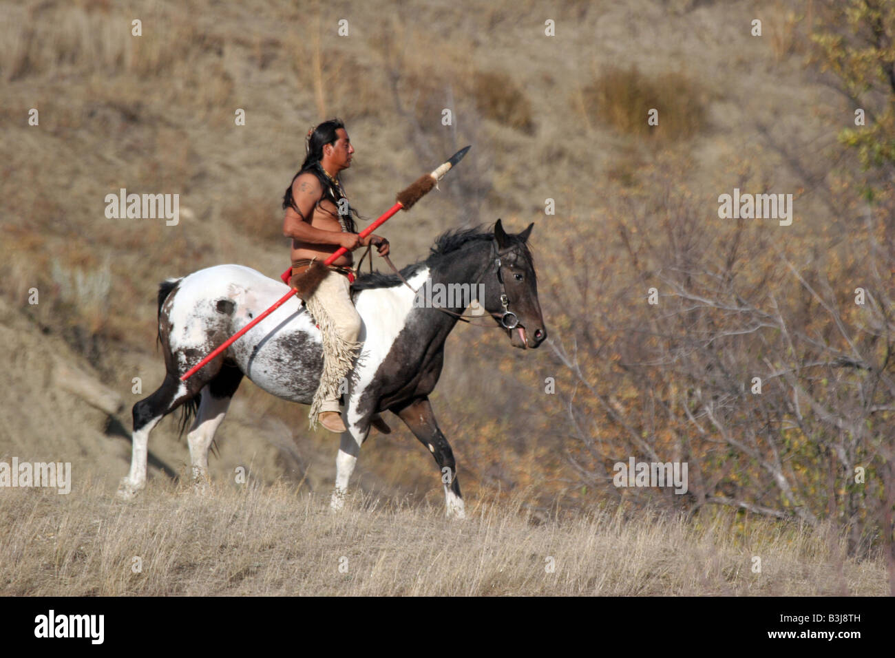 A Native American Indian on horseback on the reservation in South Dakota Stock Photo