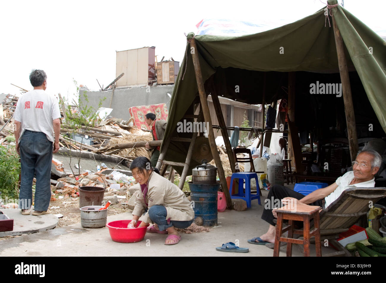 Family in makeshift tent outside their home destroyed by the earthquake of 12 May 2008 in Sichuan, China - Stock Image