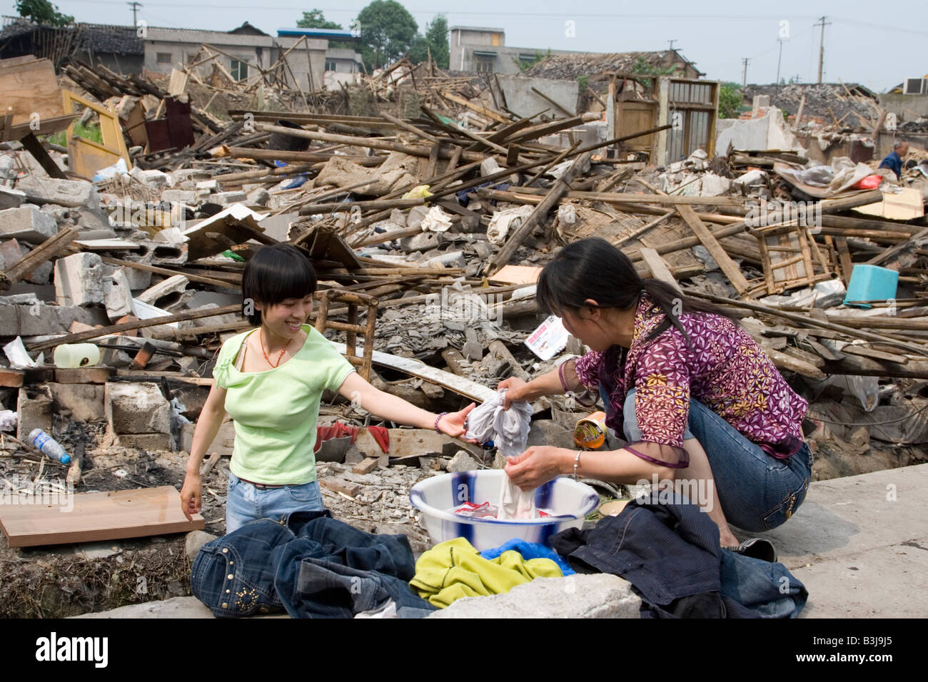 Two survivors of earthquake in Sichuan on May 12 2008 wash clothes outside their destroyed buildings. - Stock Image