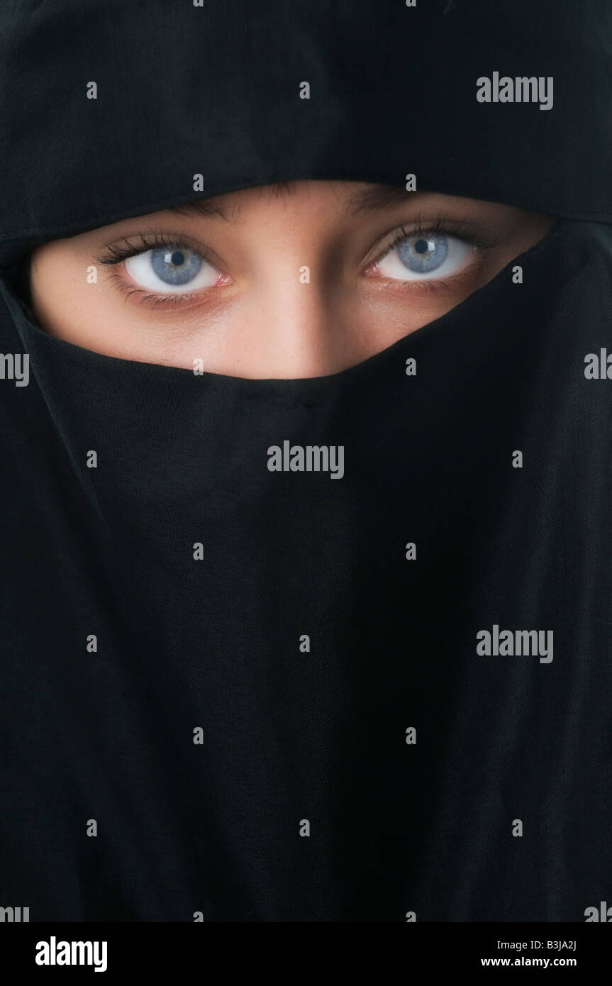 Beautiful Blue Eyed Woman looking up from inside a Niqab veil - Stock Image