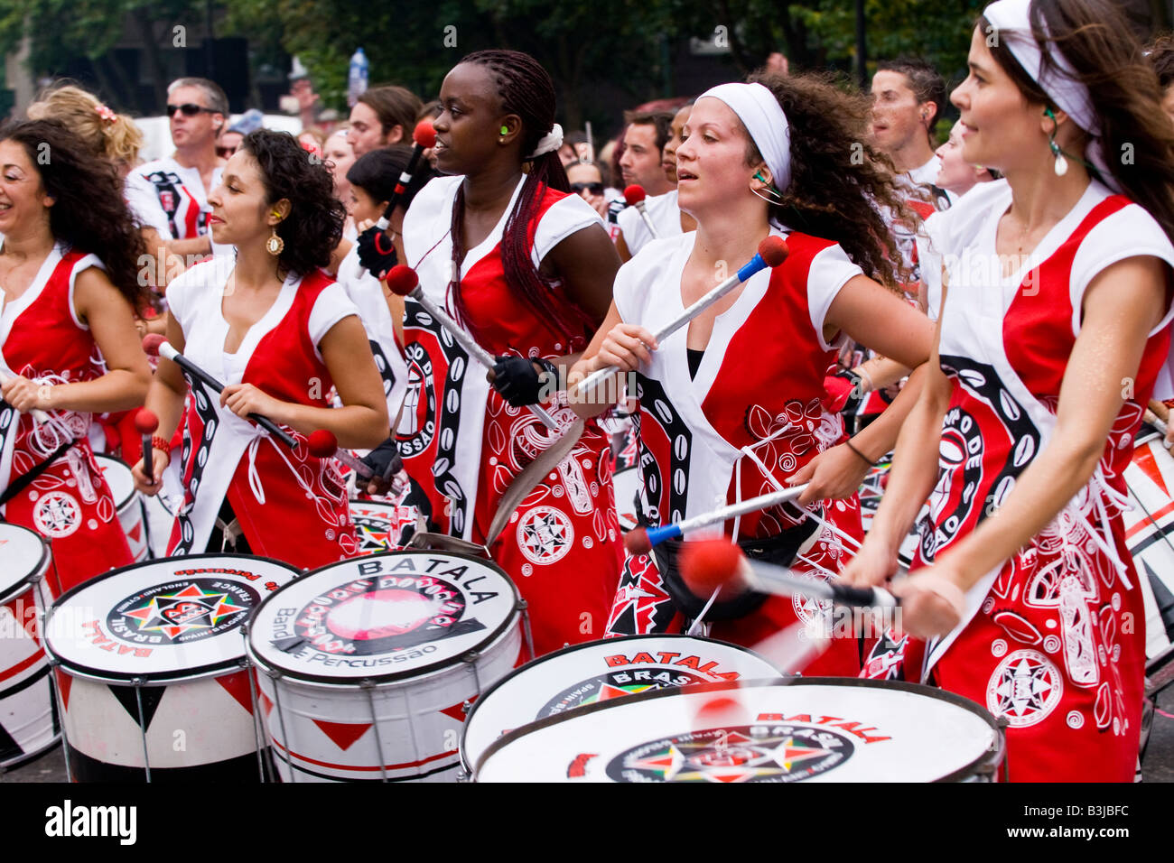Notting Hill Carnival Parade teenage young  black , brown & white girls play drums in the famous Batala Brazilian - Stock Image
