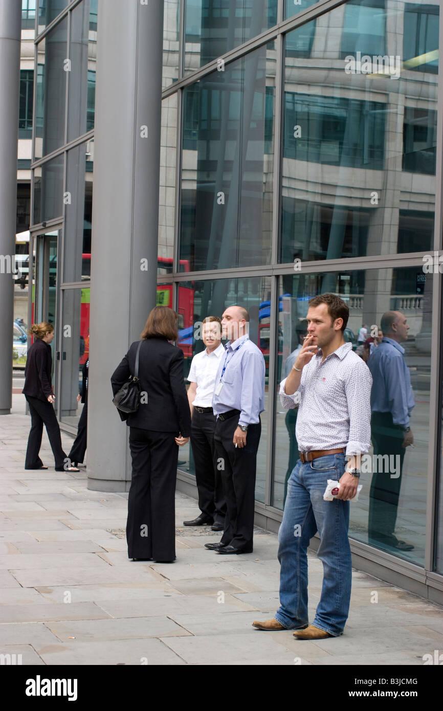 smoking smokers cigarettes smoking outside building during break - Stock Image