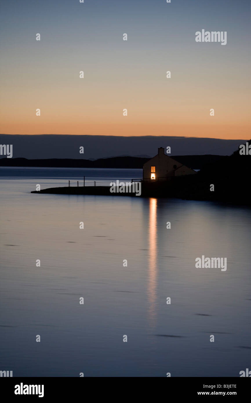 A bright window light shines across the still Loch Bay from a remote house at Stein, Waternish Point on the Isle Stock Photo