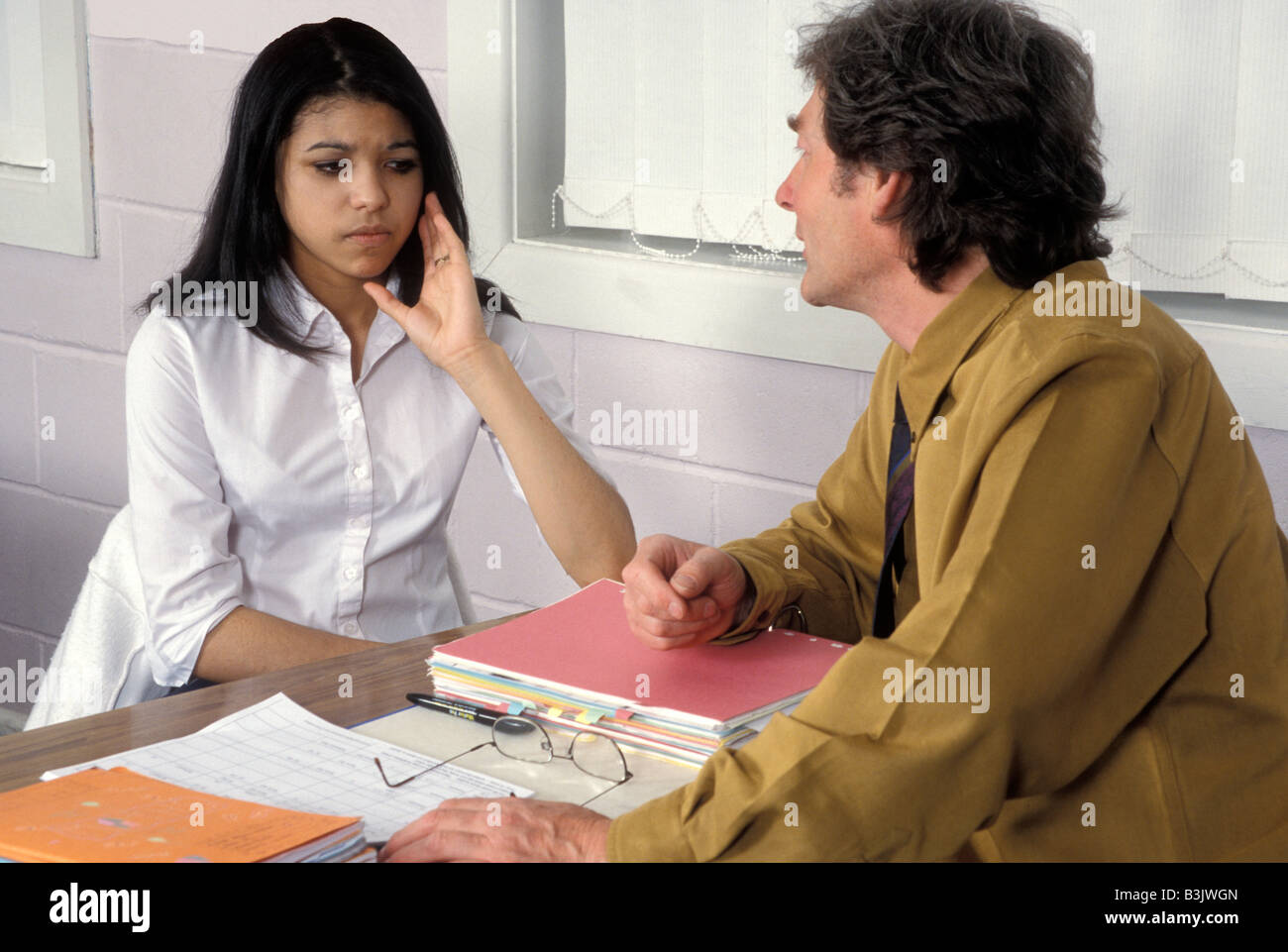 unhappy teenage girl in discussion with tutor - Stock Image