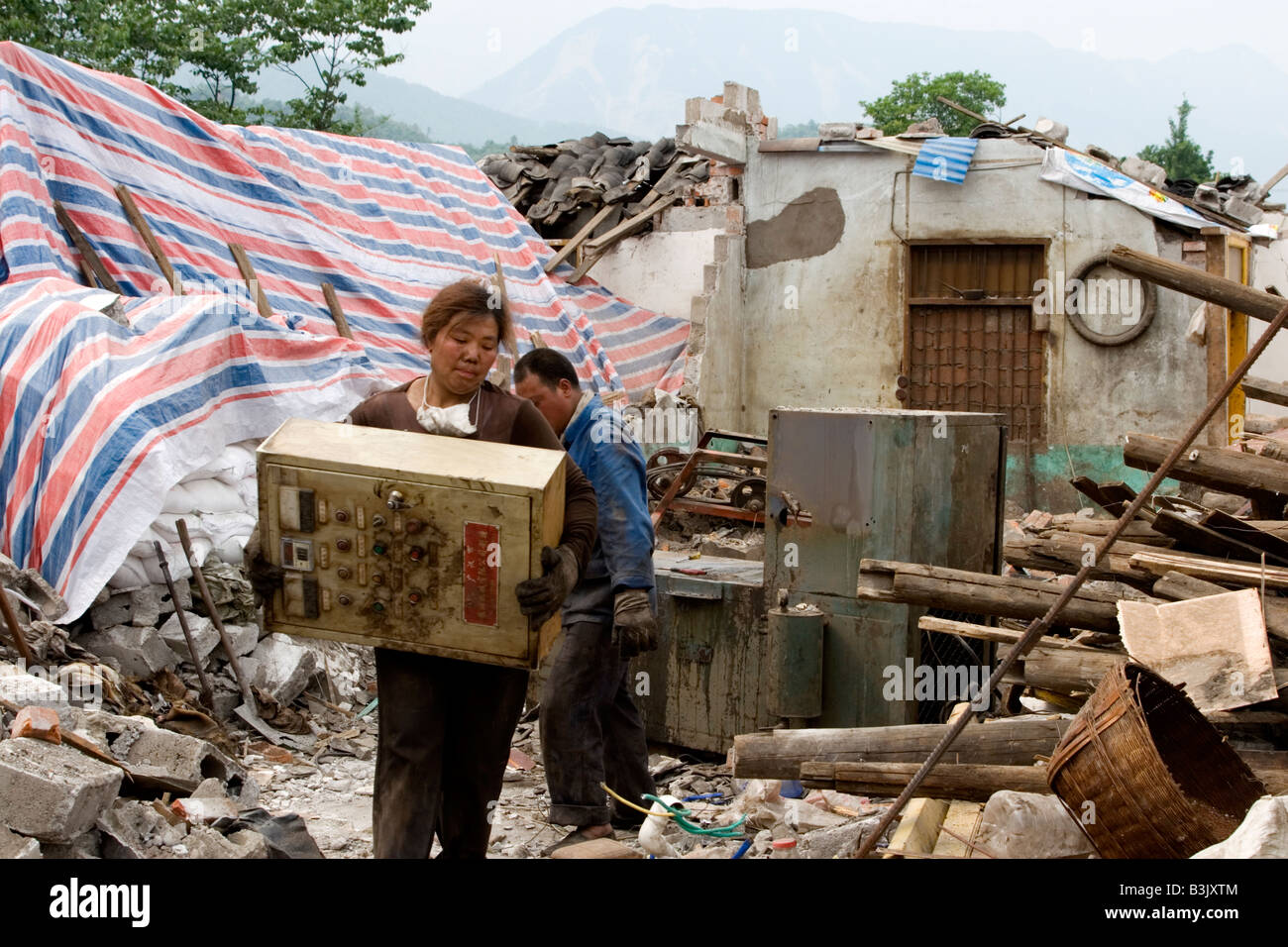 Survivors of the massive earthquake that hit Sichuan on May 12 2008 scavenge what they could from the ruins of their - Stock Image