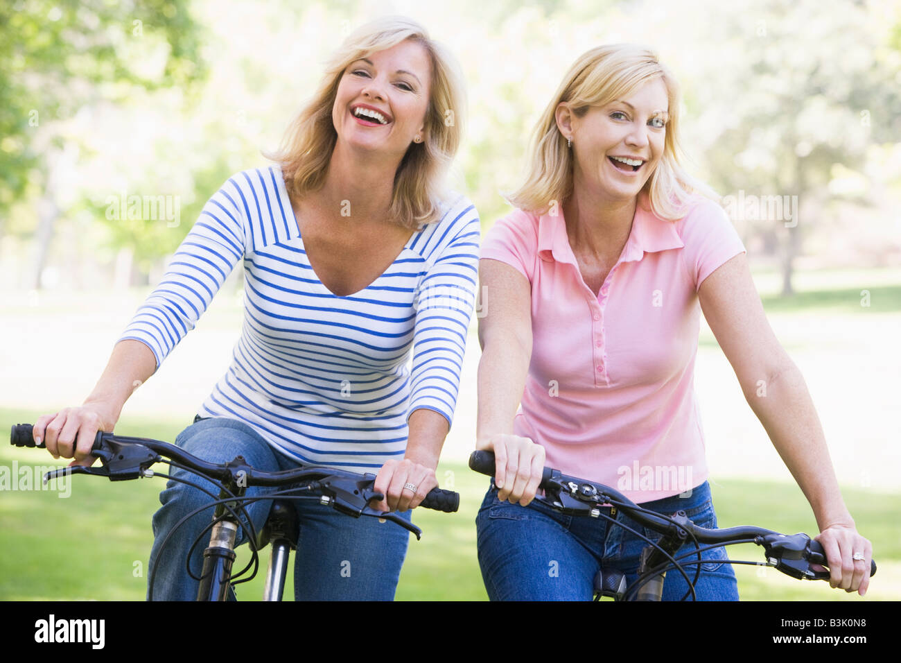 Two friends on bikes outdoors smiling - Stock Image