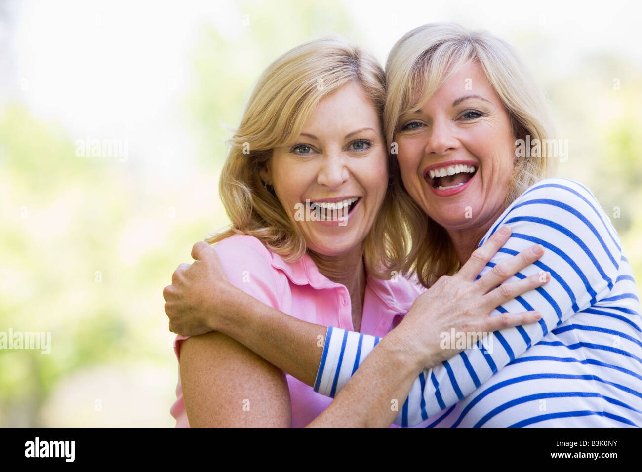 Two women outdoors hugging and smiling - Stock Image
