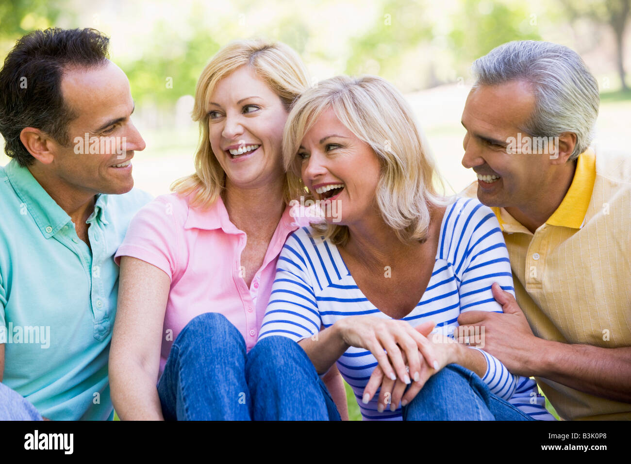 Two couples outdoors smiling - Stock Image