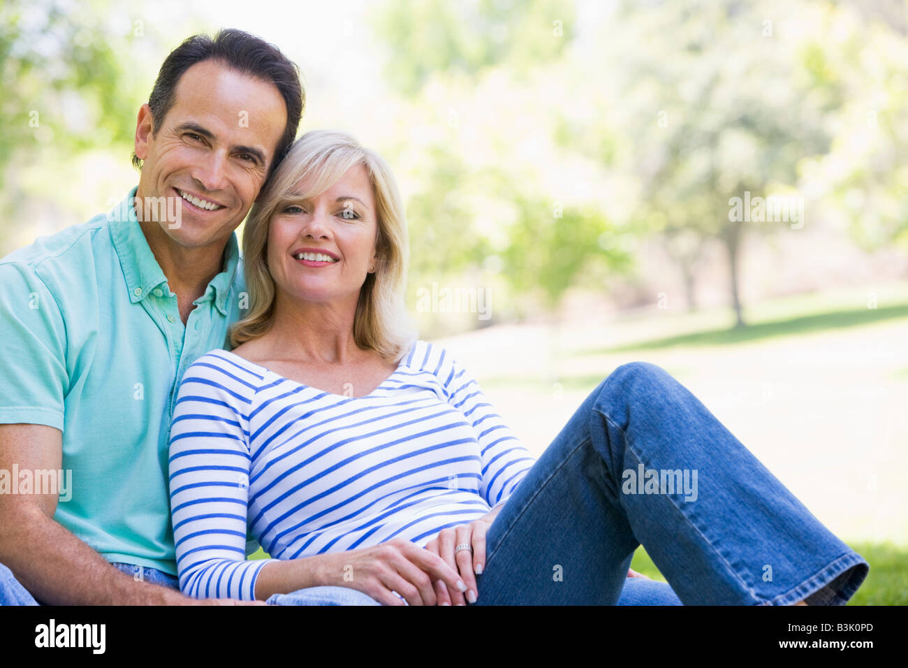Couple relaxing outdoors in park smiling - Stock Image