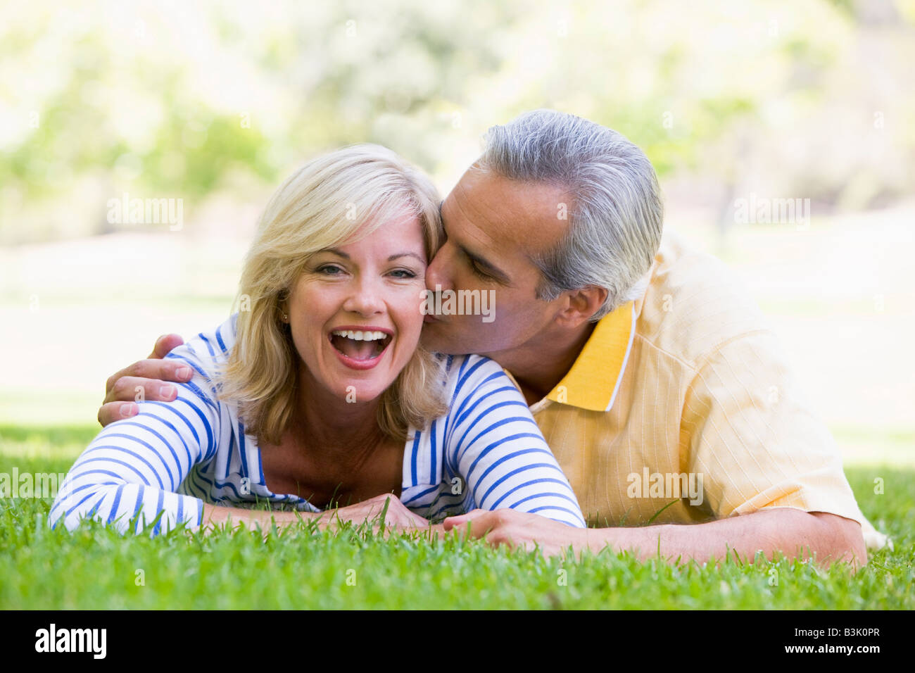Couple relaxing outdoors in park kissing and smiling - Stock Image