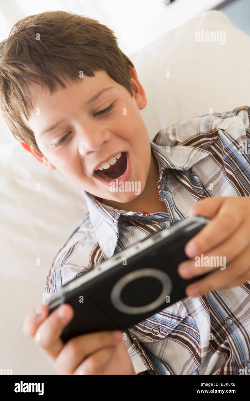 Young boy with handheld game indoors Stock Photo