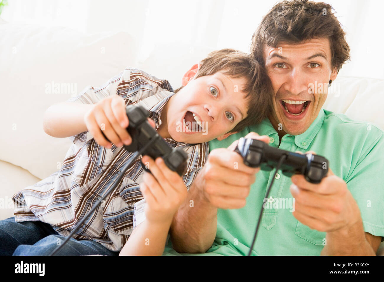Man and young boy with video game controllers smiling Stock Photo