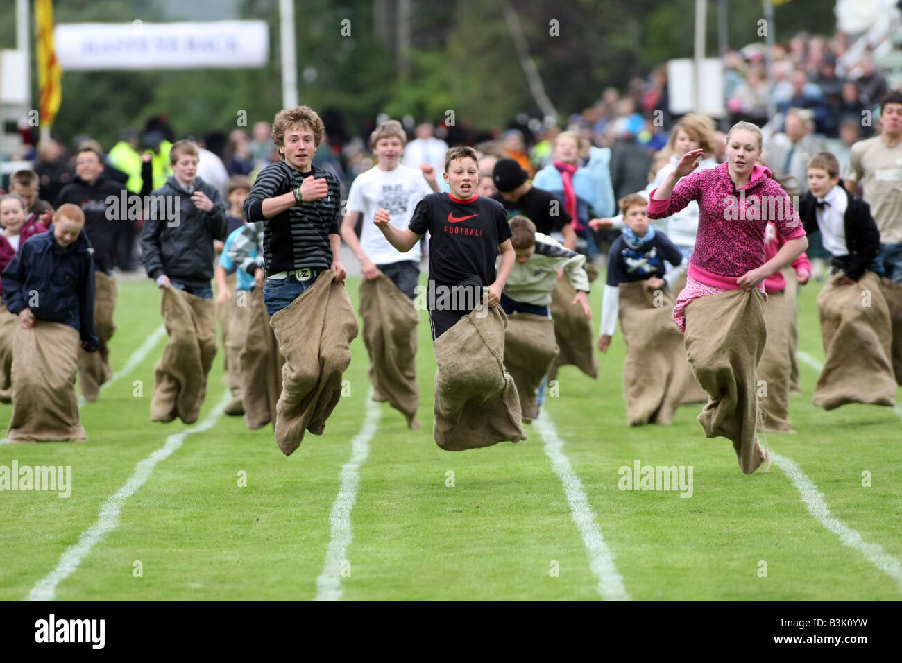 Children competing in an old fashioned traditional sack race in the UK - Stock Image