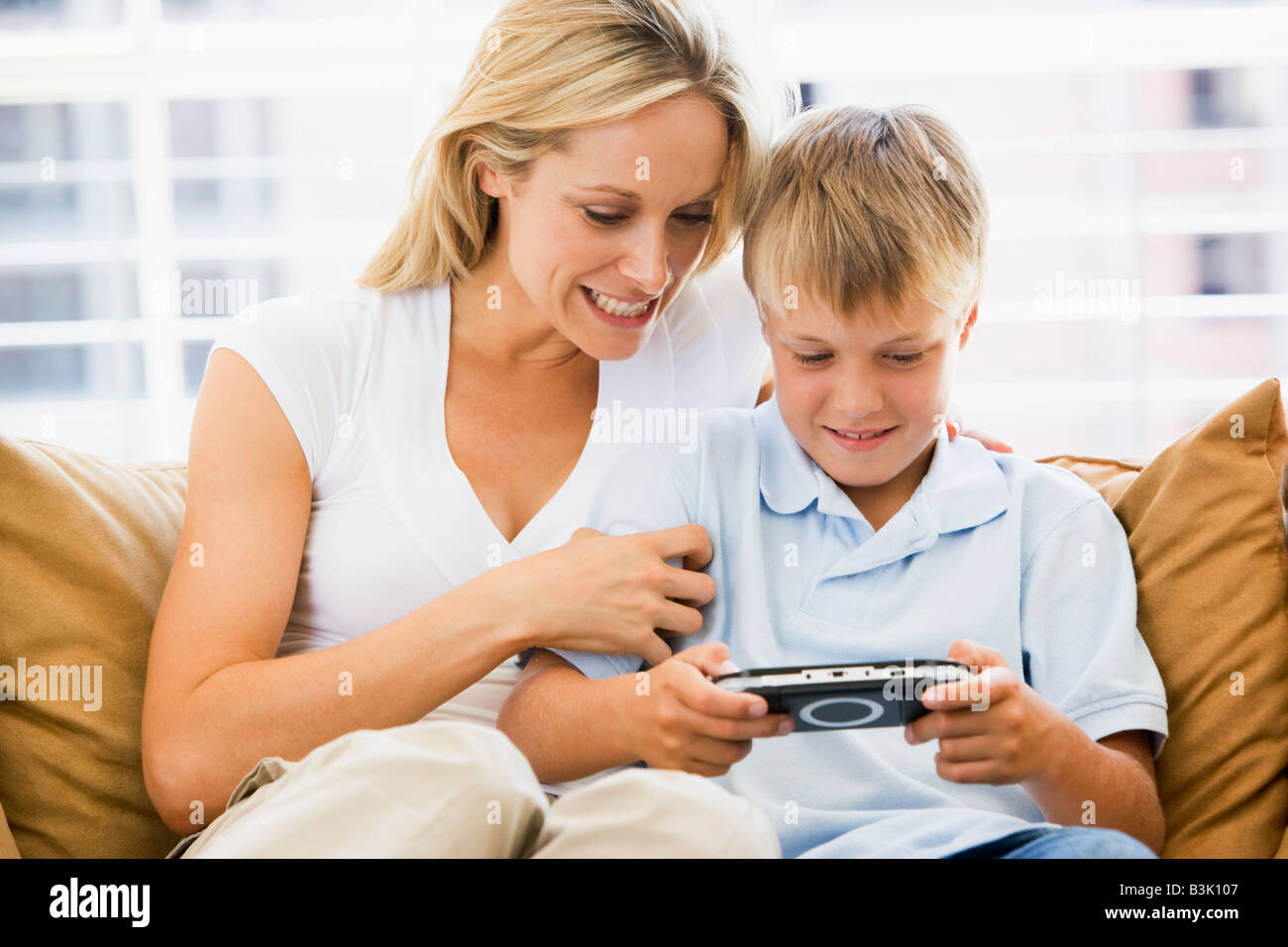Woman and young boy in living room with handheld video game smiling Stock Photo