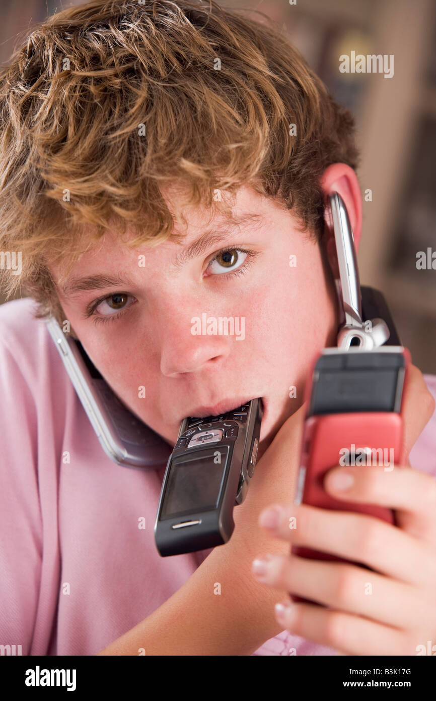 Young boy in bedroom holding many cellular phones - Stock Image