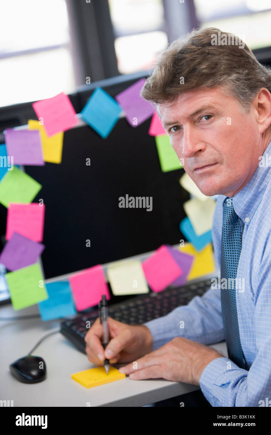 Businessman in office at monitor with notes on it writing - Stock Image