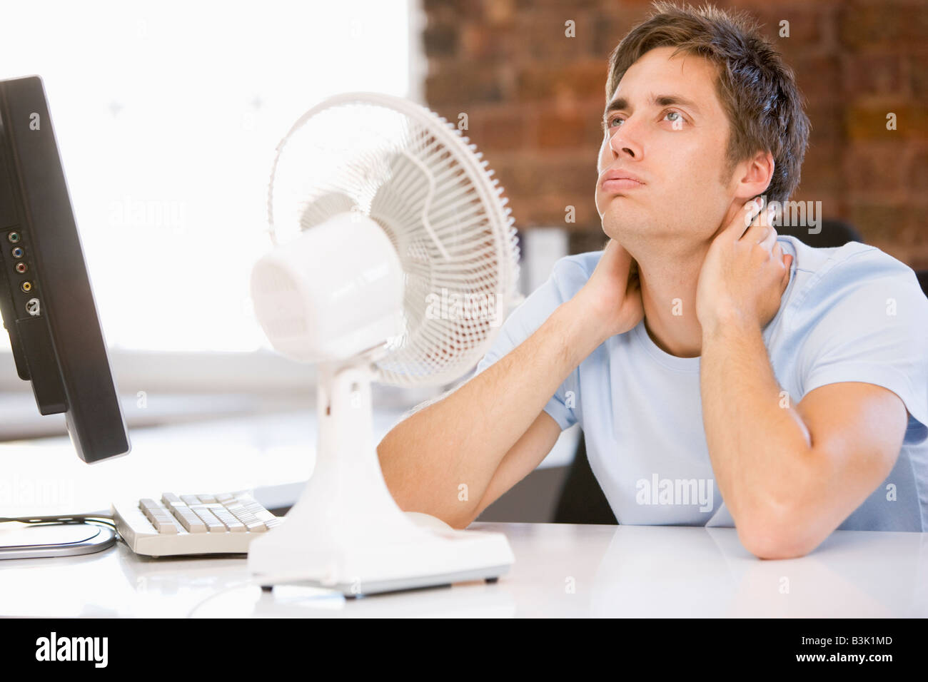 Businessman in office with computer and fan cooling off - Stock Image