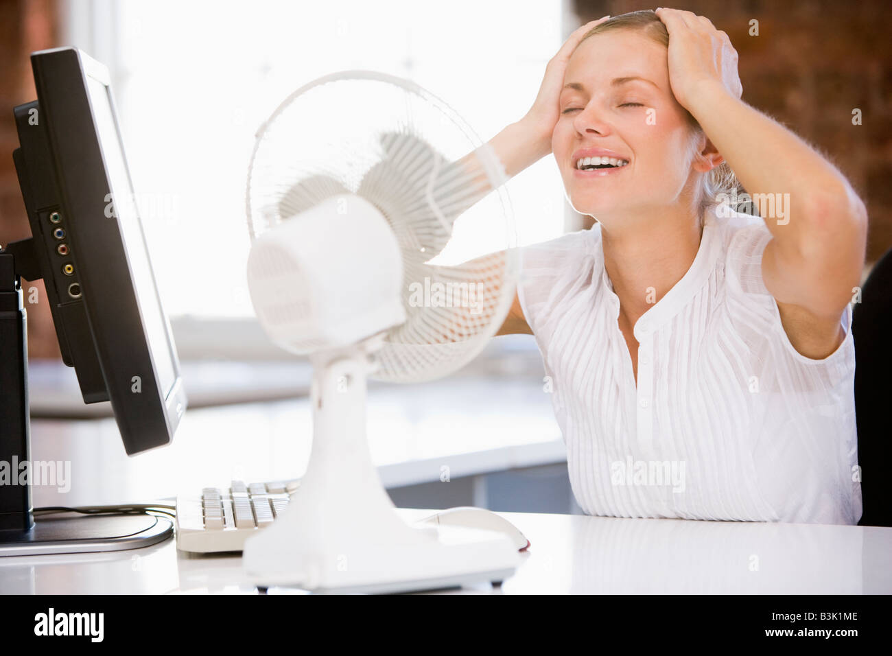 Businesswoman in office with computer and fan cooling off - Stock Image