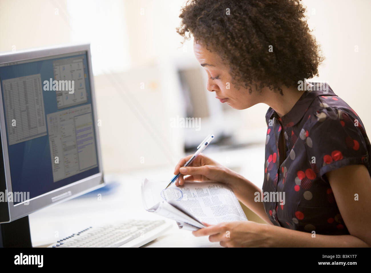 Woman in computer roon circling items in newspaper - Stock Image