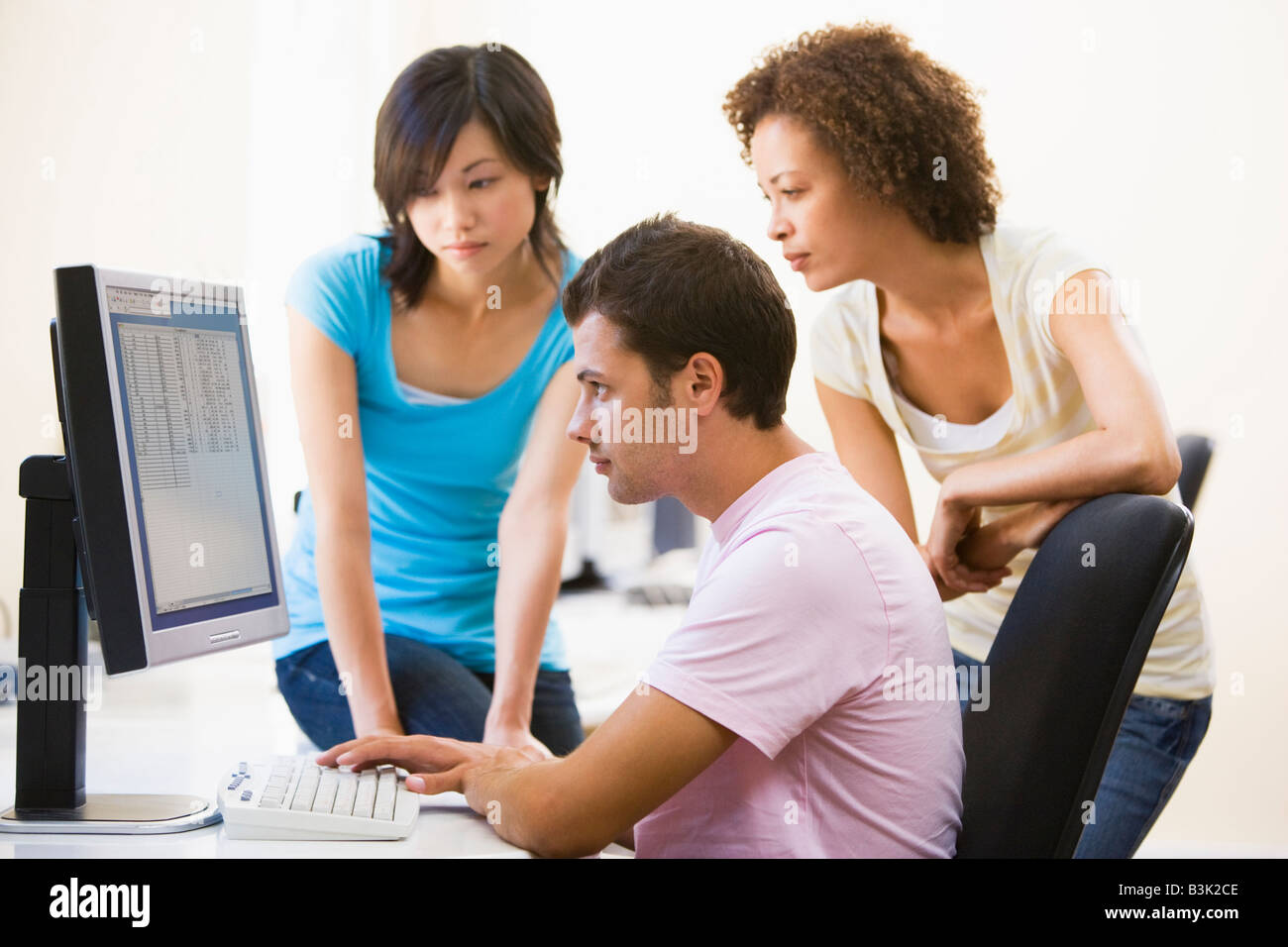 Three people sitting in computer room looking at monitor - Stock Image