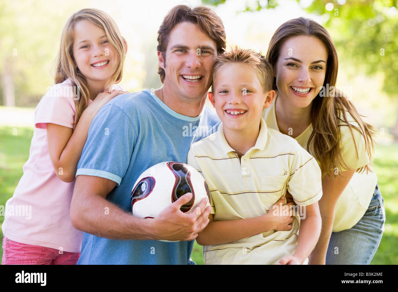 Family standing outdoors holding volleyball smiling - Stock Image