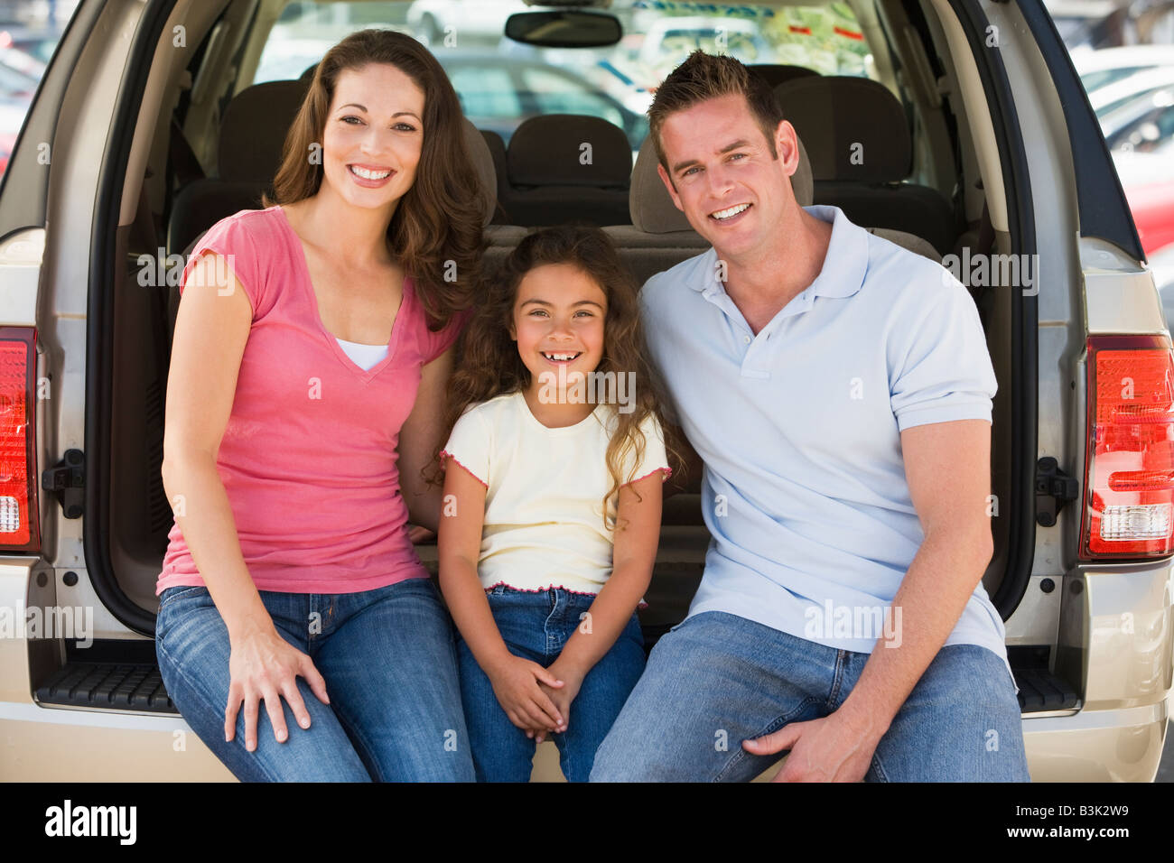 Family sitting in back of van smiling - Stock Image